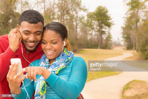 Young African descent couple listen to music. Smart phone. Earbuds.