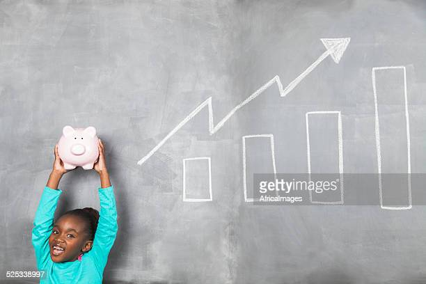Young african doing well with her piggy banks savings