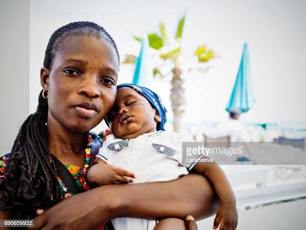 Joven madre emigrante africana con bebé