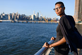 Young african american fashionable usiness woman outdoors in front of Manhattan skyline