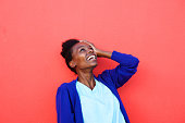 Portrait of young african female laughing with her hand on head against red background