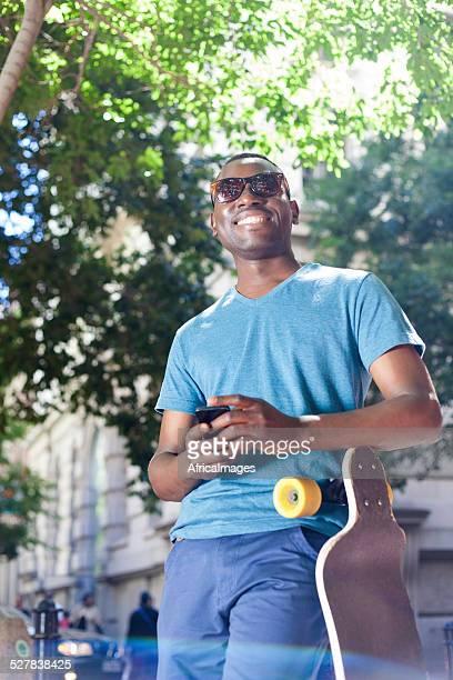 Afrique jeune homme s'appuyant sur son board envoyant un texte.