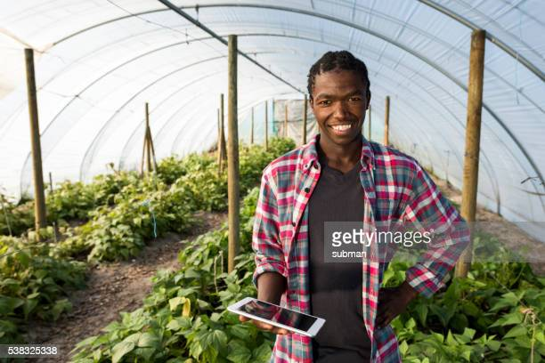 Young African male smiling with tablet in greenhouse