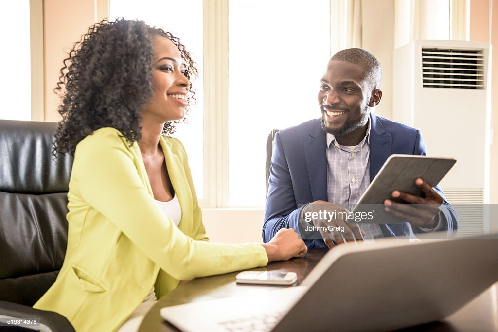 Young African man and woman in office with tablet : Stock Photo