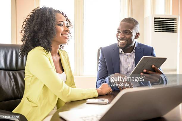 Young African man and woman in office with tablet