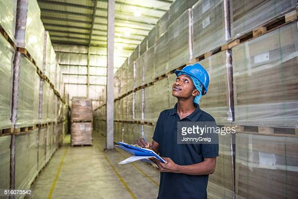 Young African man checking stock in aluminium plant