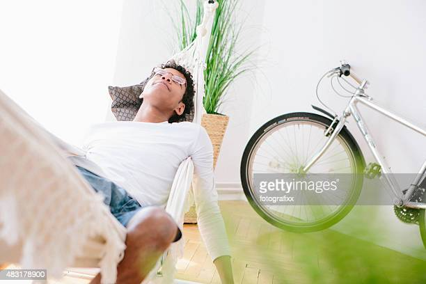 young african man relax in hammock, bicycle in background