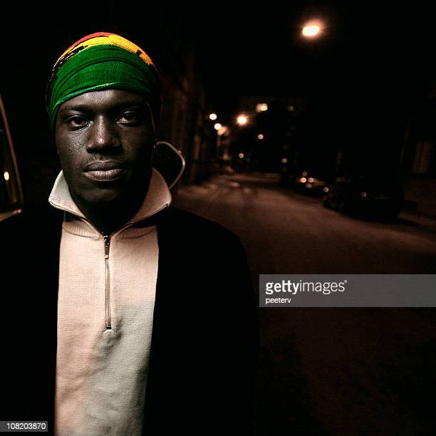 Young African Man Standing on Street at Night