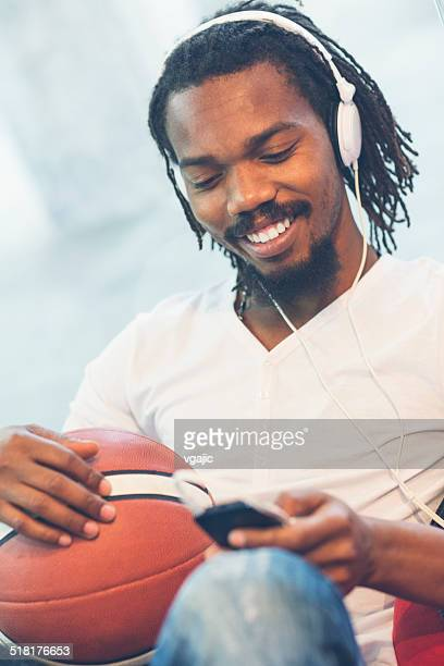 Young African Man Typing on his smart phone.