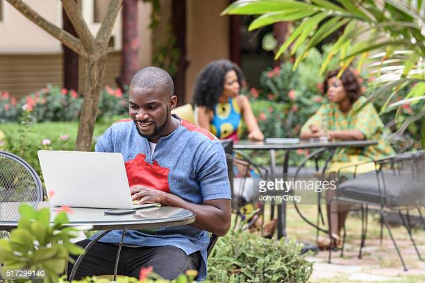 Young African man using laptop in cafe garden using