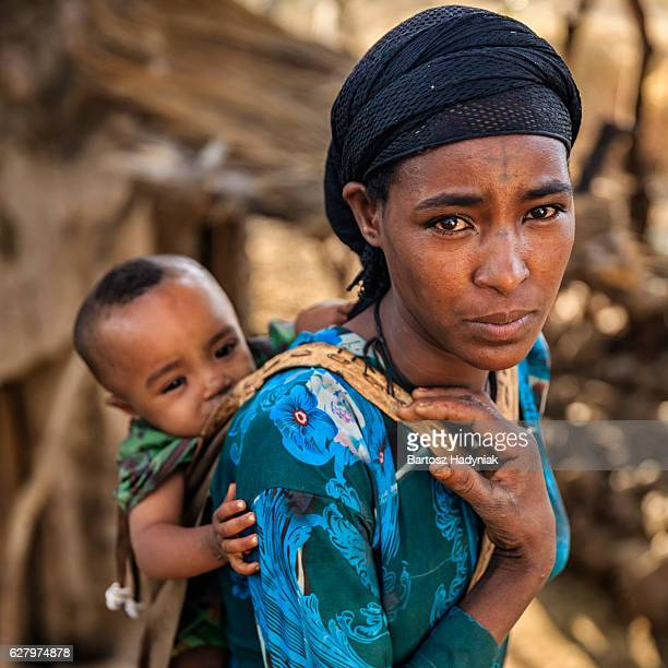 Young African mother carrying her baby on back, East Africa