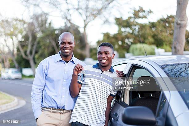 Young african teenaged boy and his father standing next to his first car , Cape Town, South Africa
