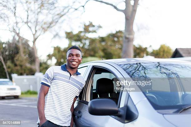 Young african teenaged boy standing next to his first car , Cape Town, South Africa