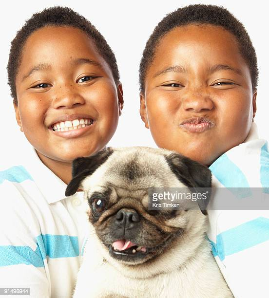 Young African twin brothers holding small dog