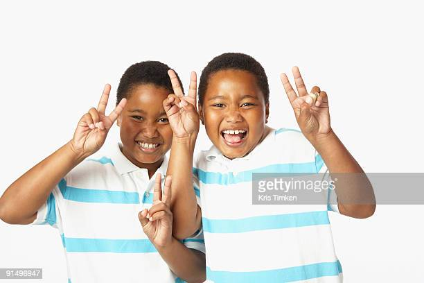Young African twin brothers smiling and making peace sign