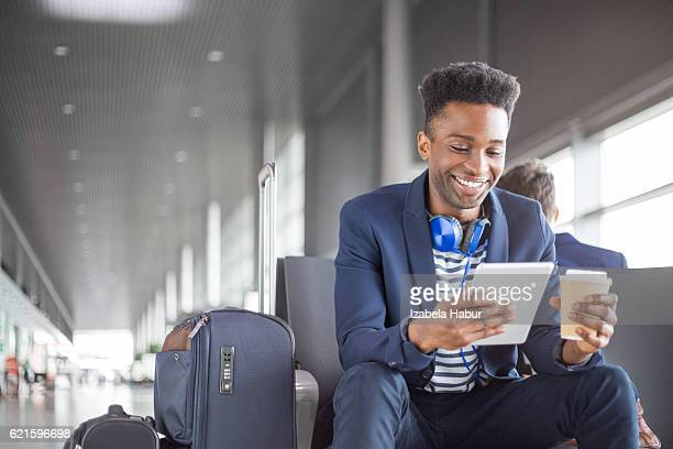 Young african using digital tablet airport lounge