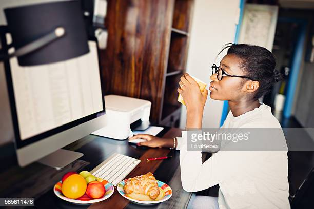 Young African woman beginning her day in front of computer