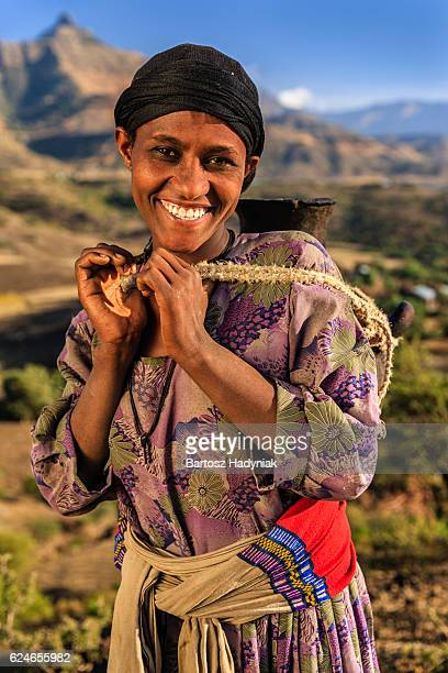 Young African woman carring water to her house, Ethiopia, Africa