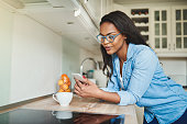 Young African woman leaning on her kitchen counter at home reading text messages on a cellphone and drinking a cup of coffee