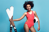 Young african female wearing swimsuit isolated on yellow wall with winter sport equipment standing holding helmet and skis looking camera smiling cheerful