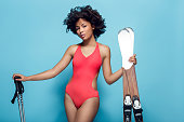 Young african female wearing swimsuit isolated on yellow wall with winter sport equipment holding skis and ski poles looking camera serious