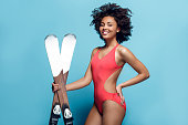Young african female wearing swimsuit isolated on yellow wall with winter sport equipment posing holding skis looking camera confident smiling cheerful