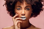 Young african female white lips makeup isolated on pink wall looking camera touching lips sensual