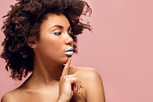Young african female white lips makeup isolated on pink wall looking aside thoughtful sensual