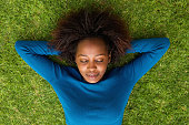 Portrait from above of a young african woman lying on grass sleeping