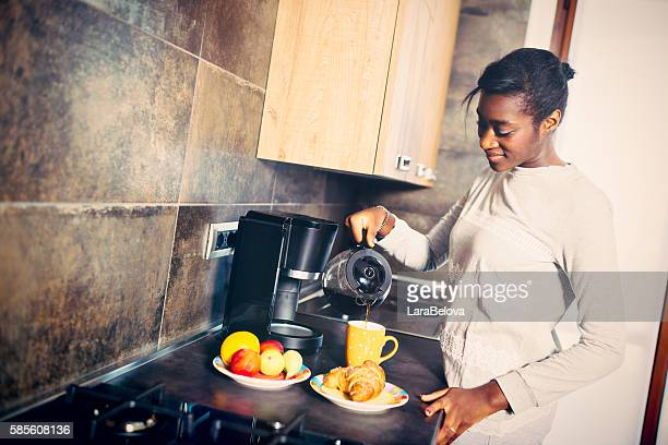 Young African Woman making coffee for breakfast