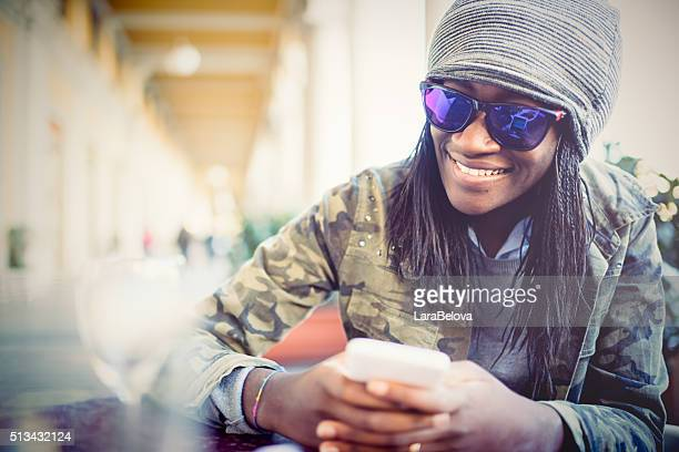 Young African woman messaging in sidewalk cafe, Italy