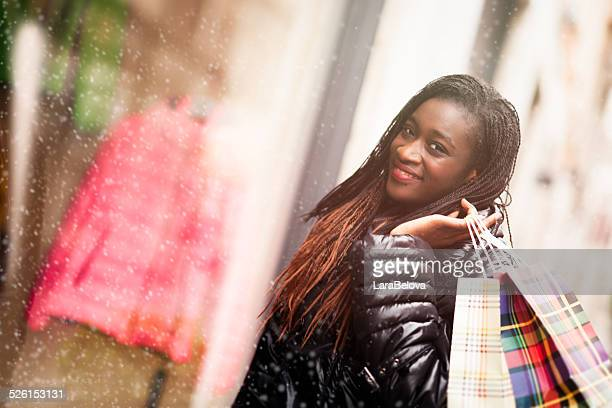 Young African woman on the street with shopping bags