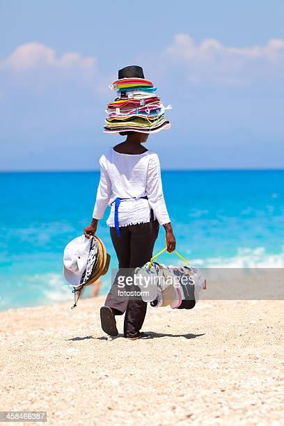 Jeune femme africaine sur la plage tropicale des chapeaux de vente