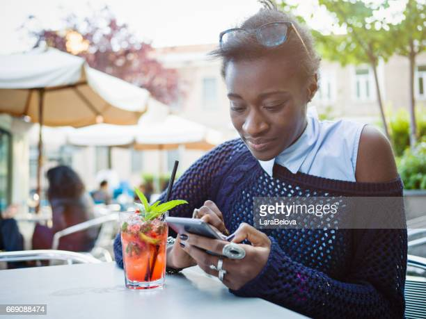 Young African Woman text messaging in sidewalk cafe