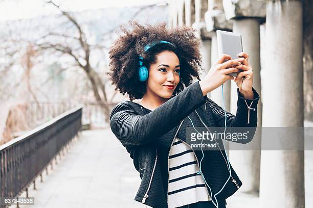 Young african woman with blue headphones making selfie near columns