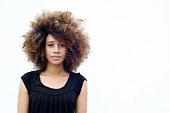 Portrait of young african woman with curly afro hair standing against white background