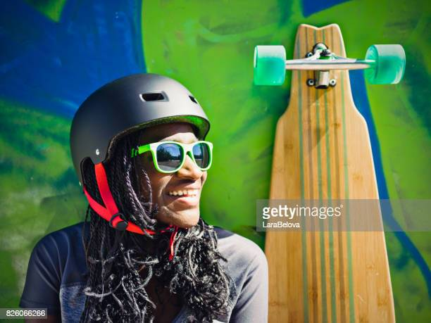 Young African woman with longboard in sakteboard's park