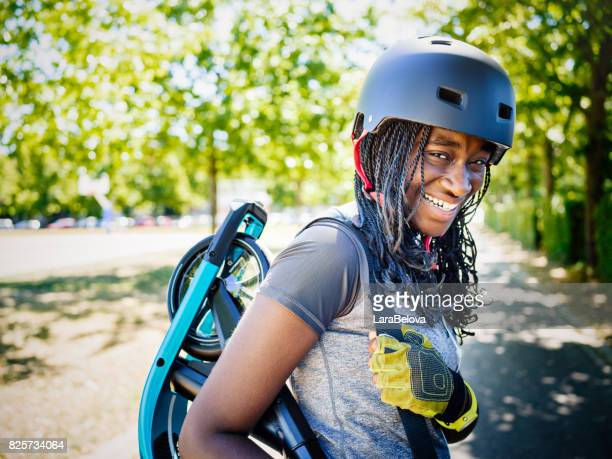 Young African woman with scooter in public park