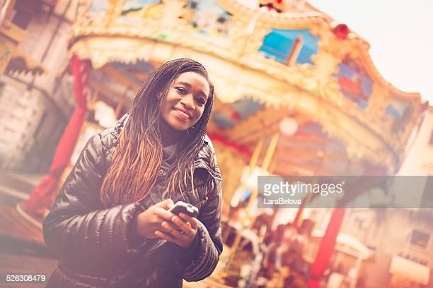 Jeune femme africaine avec téléphone intelligent sur la rue