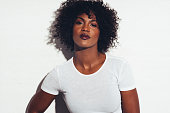 Attractive young African women with curly hair and a cool attitude standing alone against a white background