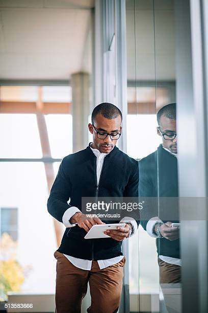 Young African-american businessman leaning against office window typing on tablet.