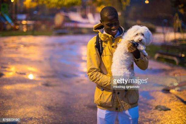 Young African-American man holding Maltese dog in the park