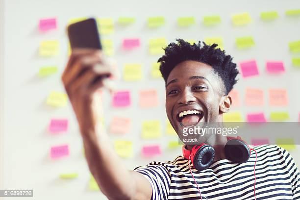 Jeune afro-américaine en prenant selfie dans un bureau