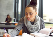 Close up image of a young female student doing assignments in library. Afro american woman taking notes from textbooks.