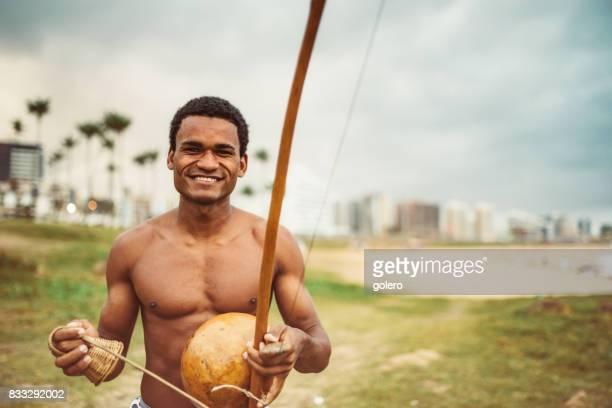 young afro-brazilan man playing berimbau at beach