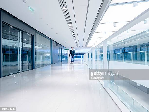 Young aisian businessman walking in architecture
