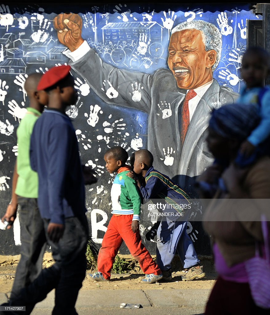 Young Alexandra's residents walk past a painting of anti-apartheid icon Nelson Mandela, on June 24, 2013 in Alexandra near Johannesburg. A statement issued by the South African government reported that former South African president Nelson Mandela's health was in a critical stage after his condition in hospital worsened over the course of 24 hours.