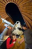 DEU Deutschland Berlin Junge HobbyAstronomen an einem Spiegelteleskop in einer Kuppel der Archenhold Sternwarte | DEU Germany Berlin Young amateur...