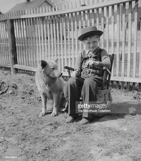 Young American boy in short sleeved cardigan and pork pie hat sitting on a small rocking chair in the back yard with a dog sitting by his side wood...