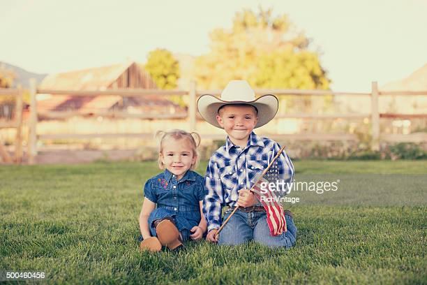 Jeune Cowgirl américaine et Cowboy avec drapeau américain